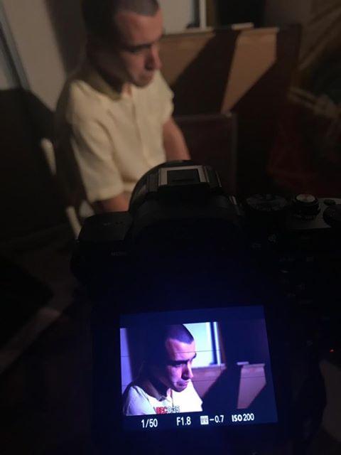 Foto desfocada de Victor sentado em uma cadeira. No rodapé da foto está uma câmera onde podemos ver o rosto dele com uma expressão triste. Ele é branco, tem cabelos raspados e usa uma camisa bege. Fim da descrição.